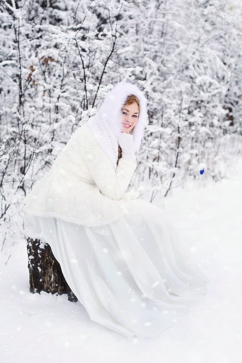 Woman sitting on a tree trunk in a snowfield