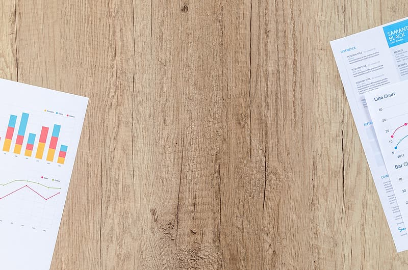Top view of brown wooden surface with two printer papers
