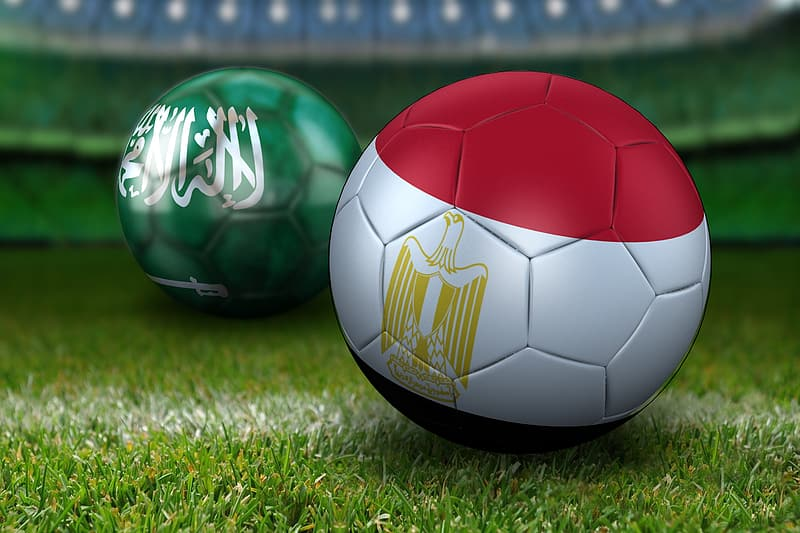 Red and white soccer ball on green grass