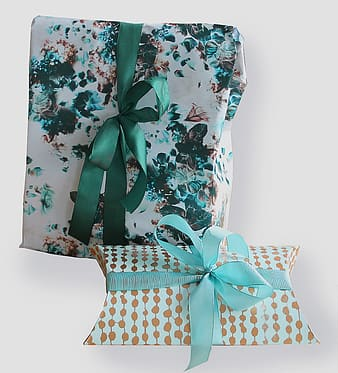 Two rectangular white and green gift boxes on white surface
