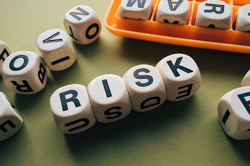 Four white-and-black risk letter dices