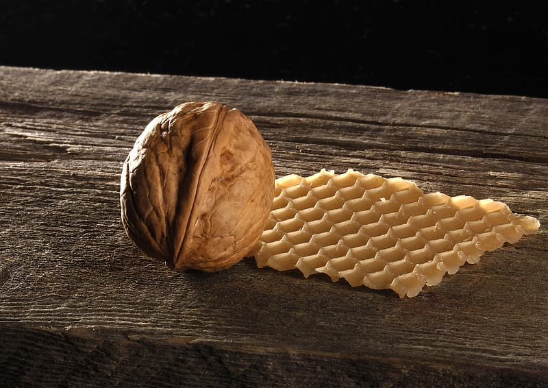Pecan nut and waffle on brown wooden surface
