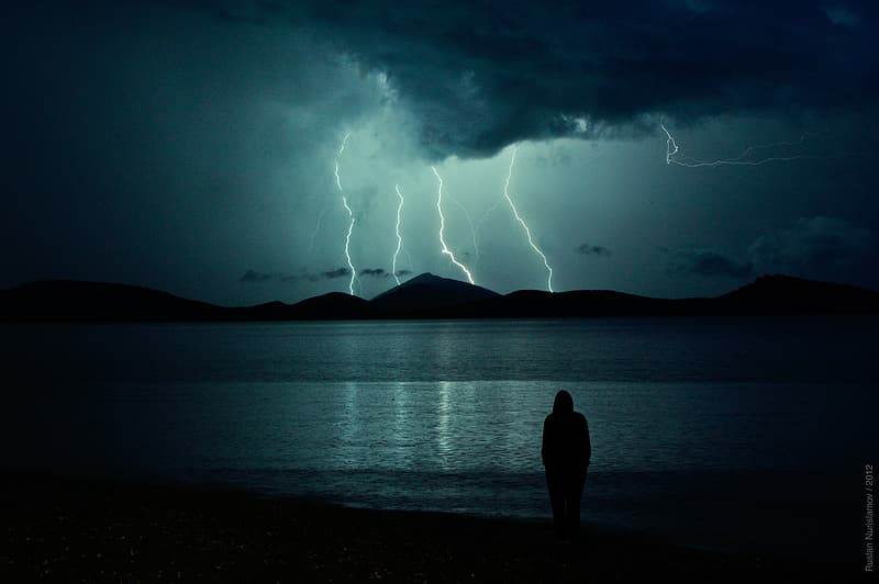 Person standing near seashore and mountain cliff with thunder