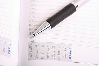 Gray click pen on white line paper with calendar