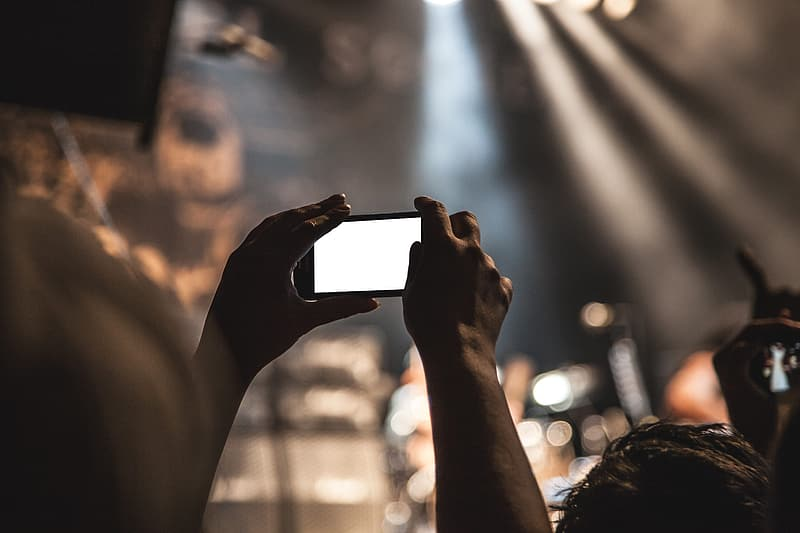 Selective focus photography of person holds smartphone in portrait mode during concert