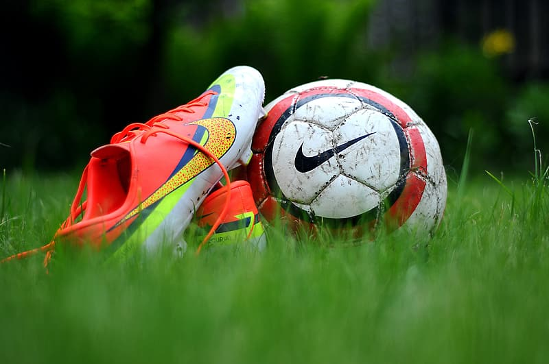 Close-up photo of cleats and soccer ball on green grass