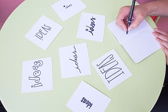 Photo of person writing ideas text in white printing papers