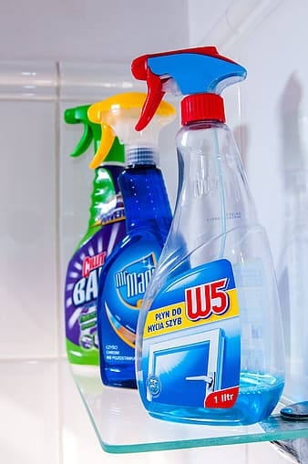 Three cleaning spray bottles on top of glass-top wall shelf