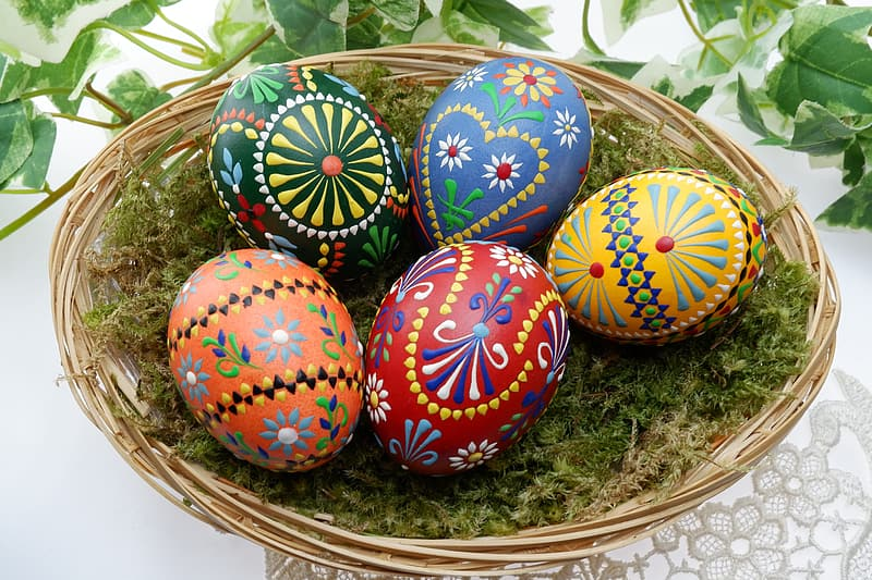 Several assorted-color Easter eggs on brown wicker basket