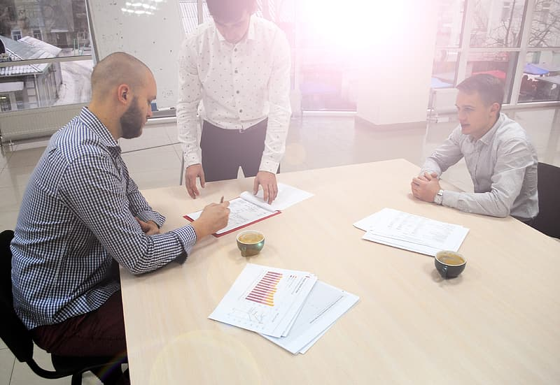 Man holding pen signing contract on brown wooden table