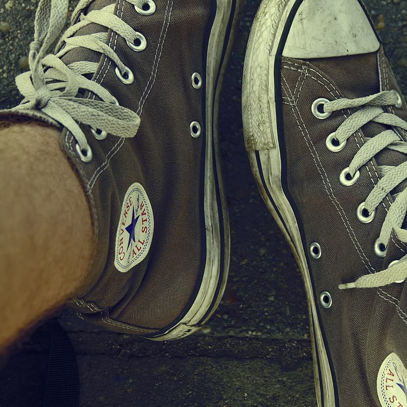 Person wearing black converse all star high top sneakers