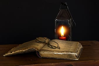 Lighted candle near books and eyeglasses