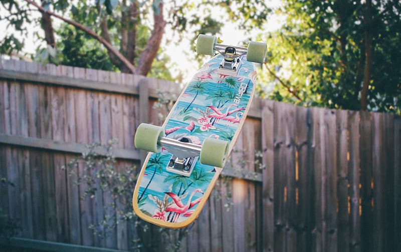 Green and black skateboard on brown wooden fence during daytime
