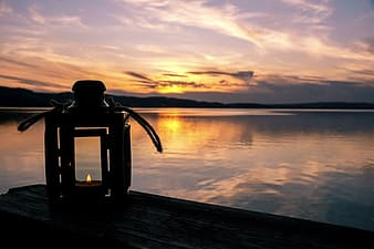 Black and gray camera on dock during sunset