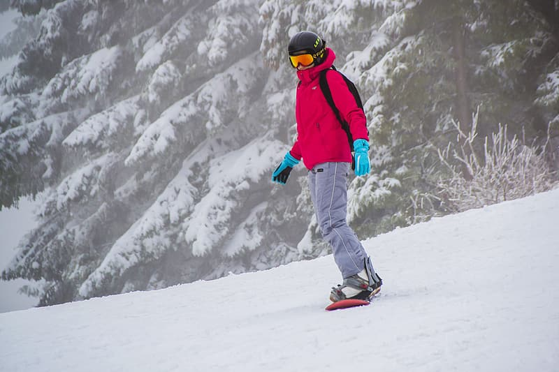 Man wearing pink jacket snowboarding in winter weather