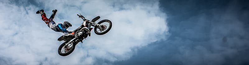 Sports photography of motocross racer holding motocross dirt bike seat while suspended on air