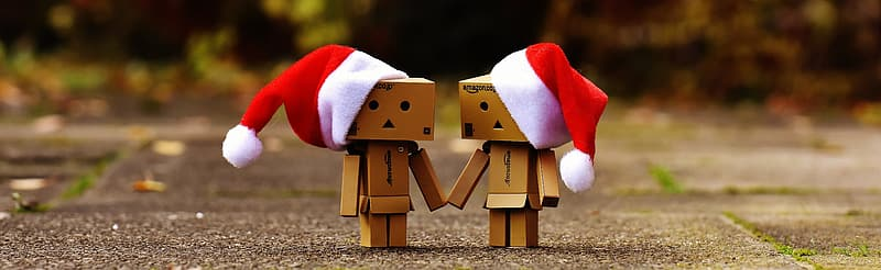 Selective focus photography of two cardboard box robots wearing Santa hat