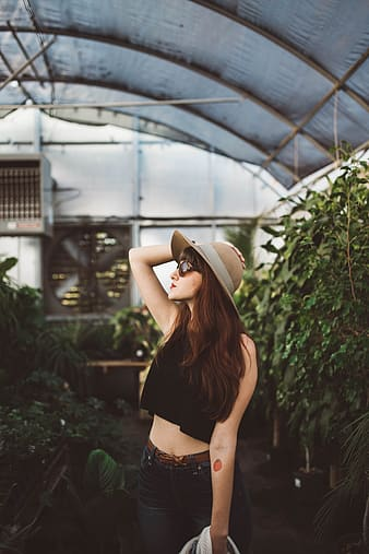 Woman wearing crop top surrounded by plants