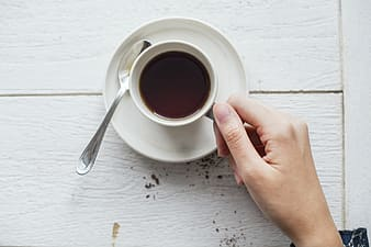 Person holding cup of coffee on white saucer beside spoon