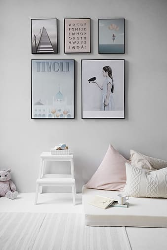 Five paintings mounted on wall above white end table