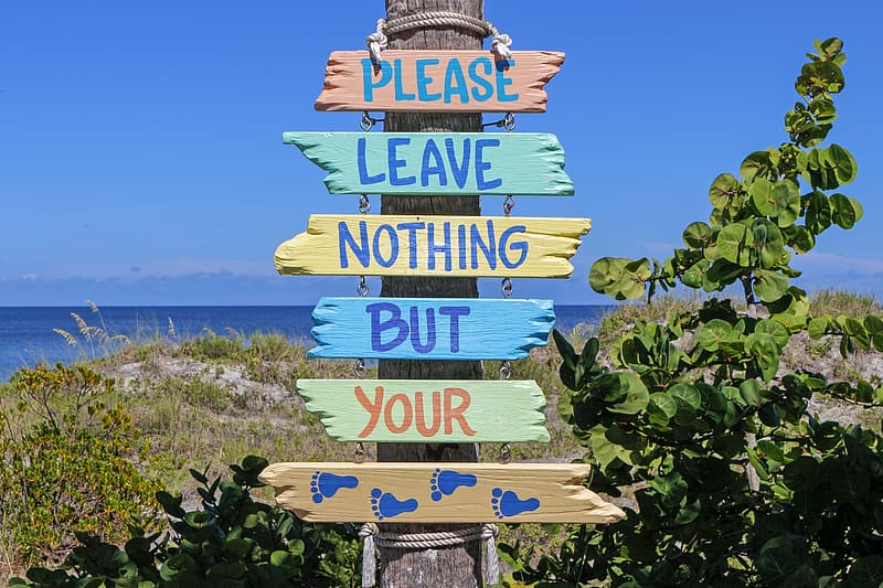 Closeup photo of Please Leave Nothing But Your Foot Prints sign