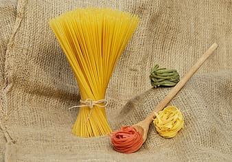 Assorted-color pasta with brown wooden ladle
