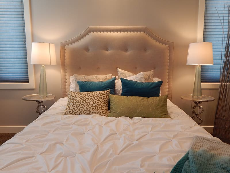 White bed sheet and tufted headboard