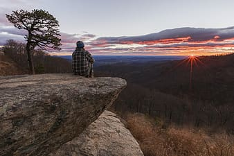Man sitting on the edge of the cliff watching golden hour