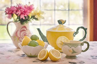 Yellow ceramic teapot with lemonade with cup beside bowl and flower centerpiece