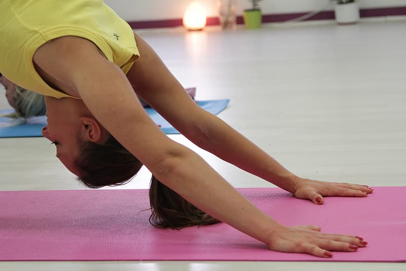 Woman doing yoga on pink yoga mat