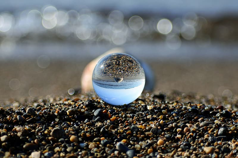 Clear glass ball on black and brown pebbles