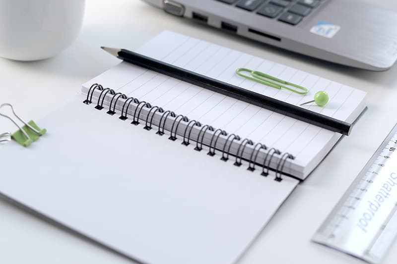 White notebook and black pencil
