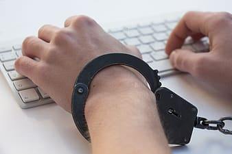 Person with handcuffs typing on the white keyboard