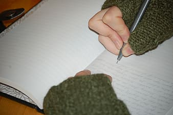 Person wearing green long-sleeved shirt when writing on notebook