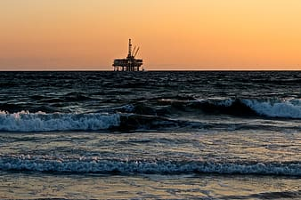 Oil rig on the sea photo during sunset