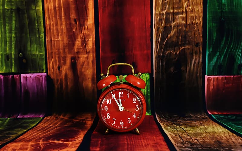 Red analog alarm clock on brown wooden surface