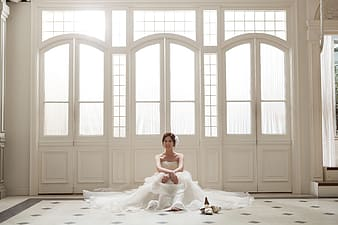 Woman wearing white floral wedding dress near window