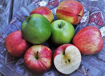 Green and red apples on white and red textile
