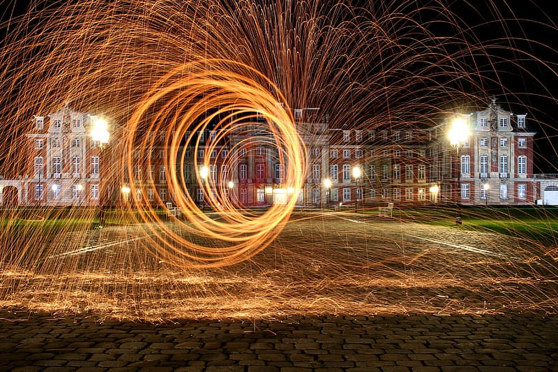 Steel wool photography in front of red concrete building