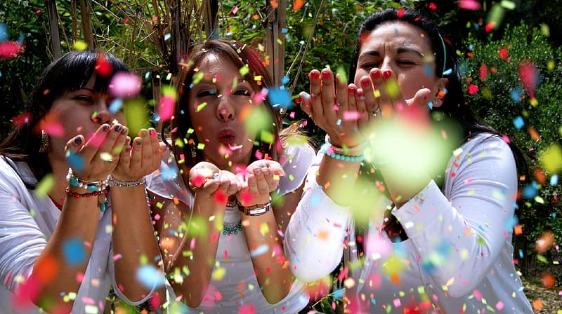 Three woman blowing assorted-color confettis