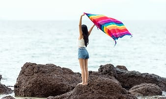 Woman in blue denim shorts holding pink yellow and blue umbrella standing on brown rock near near near near near