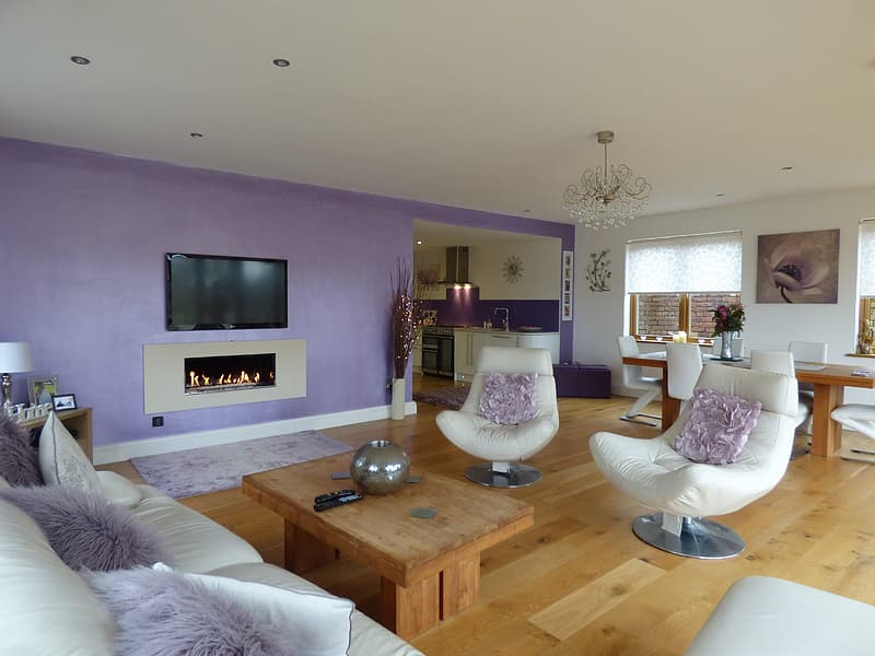 Turned off TV on wall in front of white leather sofa set with purple fleece throw pillows