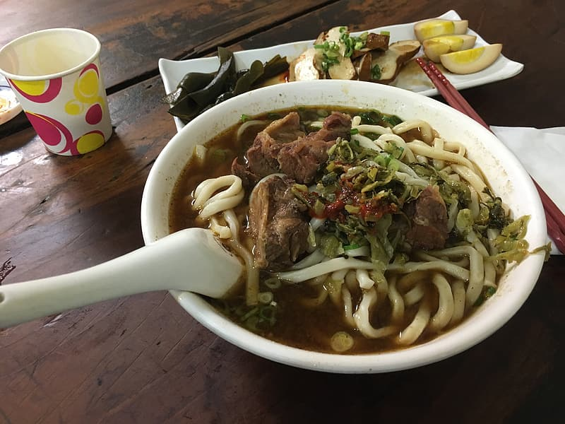 Noodle soup with meat and vegetables in white ceramic bowl