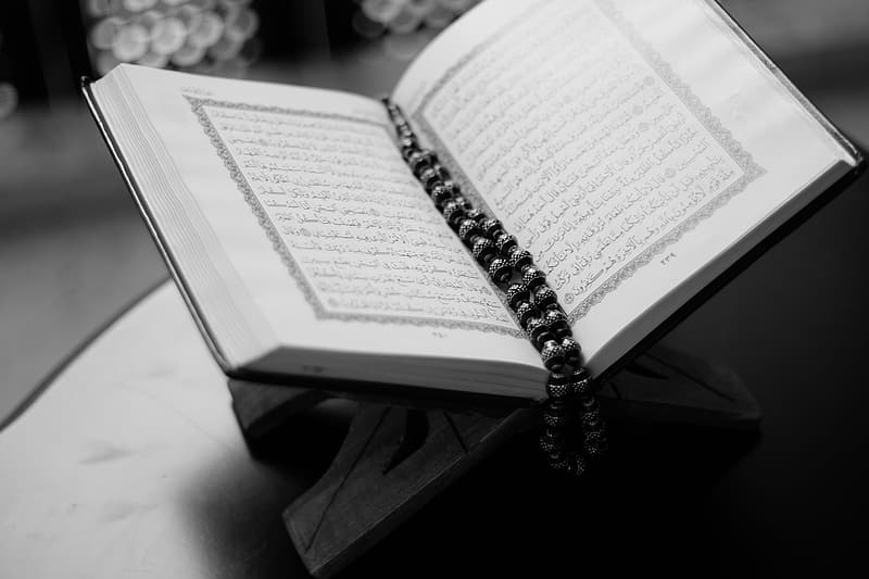 Grayscale photography of white book with tesbih prayer beads bookmark on top