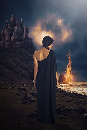Woman in black dress standing on sand near bonfire