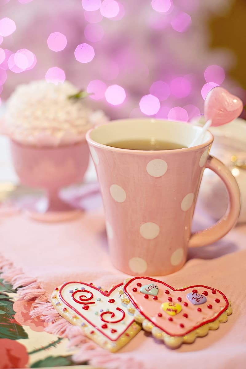 Pink ceramic mug on white and red table cloth
