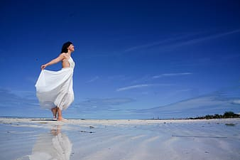 Woman in white sleeveless dress on shore under blue sunny sky