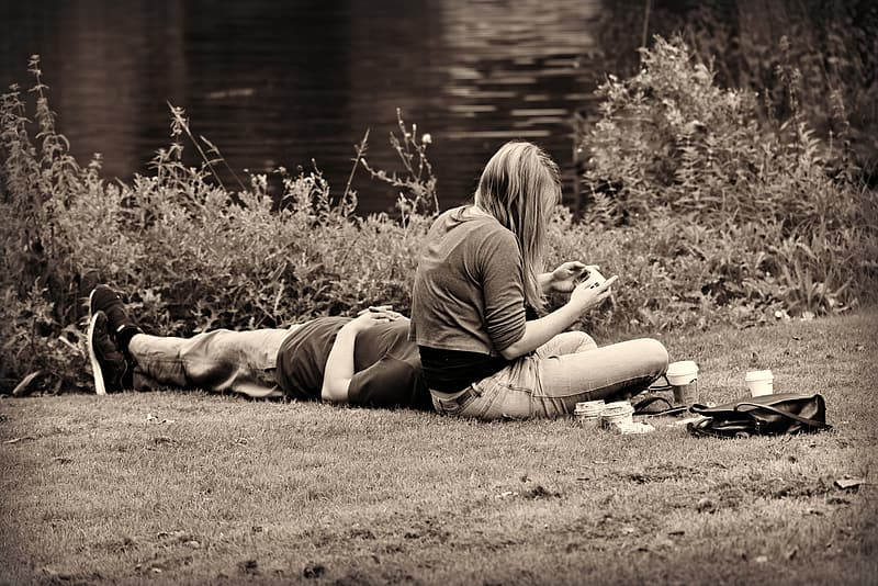 Woman in black shirt and black pants lying on ground near lake during daytime