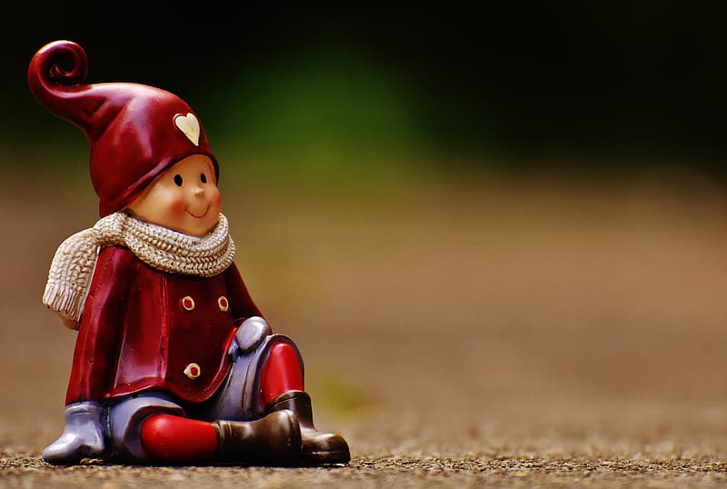 Close up photo of red and blue boy sitting ceramic figurine