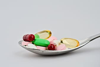 Assorted medicine capsules on stainless steel spoon